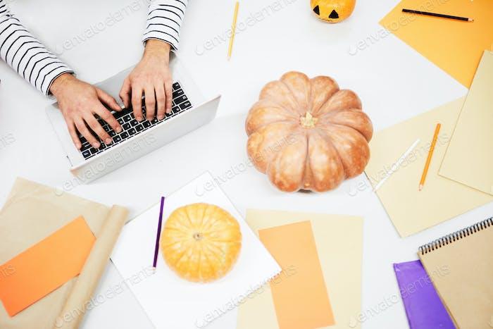 Tabelle voller orange Papiere und Kürbisse