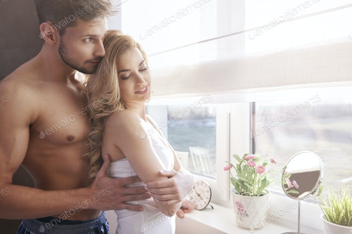 Charming couple standing next to the brightly lit window