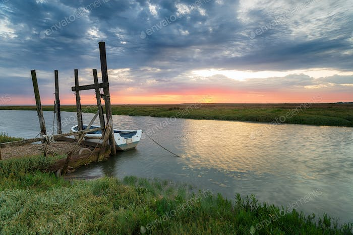 Sunrise over a boat moored to an old wooden jetty at Thornham