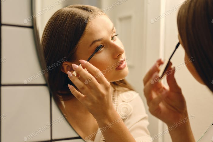 Young beautiful woman in white dress standing near mirror thoughtfully applying mascara in bathroom