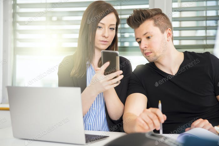 Business People Using Smart Phone At Desk In Office