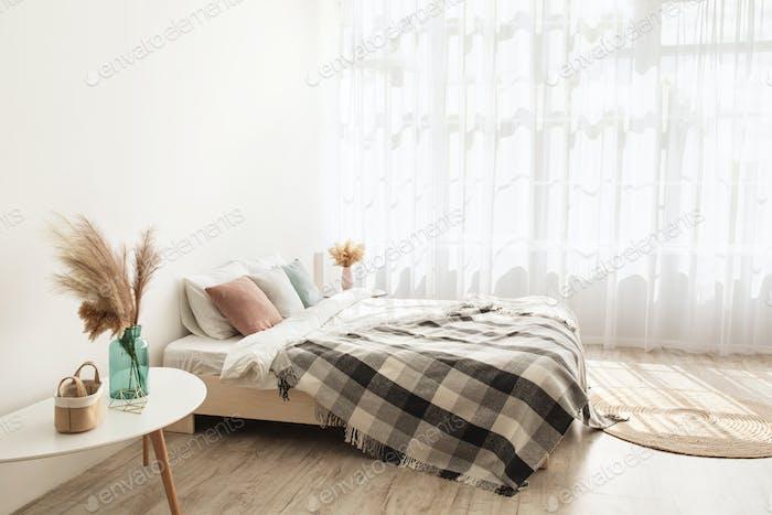 Leichter Boho-Stil und Immobiliendesign Bett mit Kissen und Decke, Teppich, Tische mit trocken