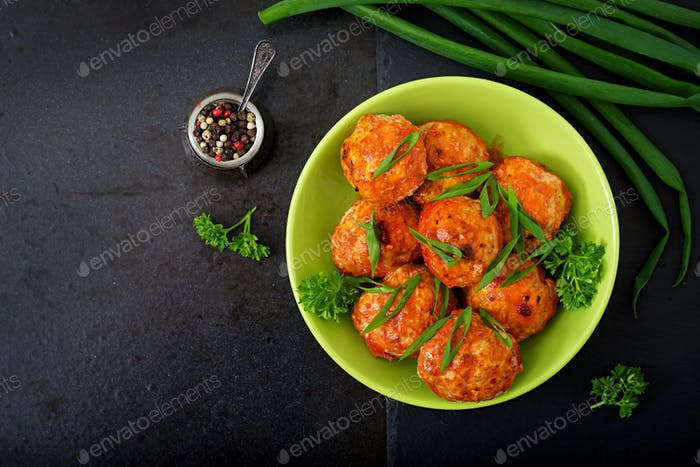 Baked meatballs of chicken fillet in tomato sauce. Flat lay. Top view