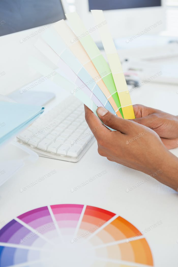 Designer working at desk holding colour samples in his office