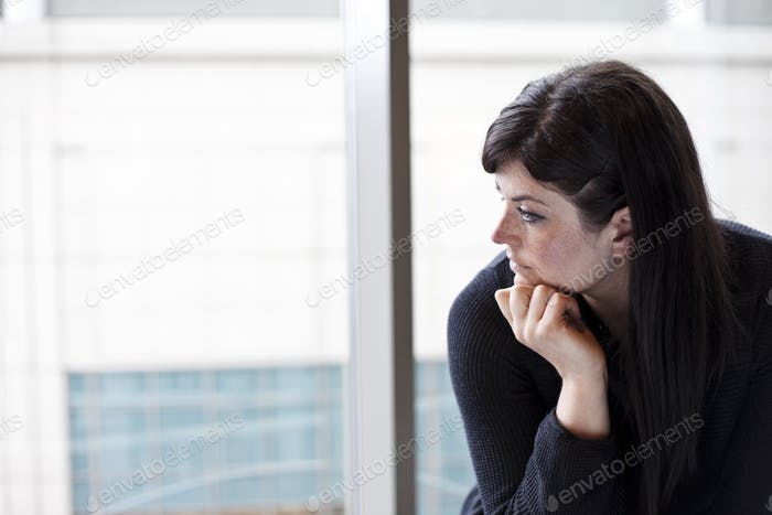 A businesswoman looking out a window at a convention center.