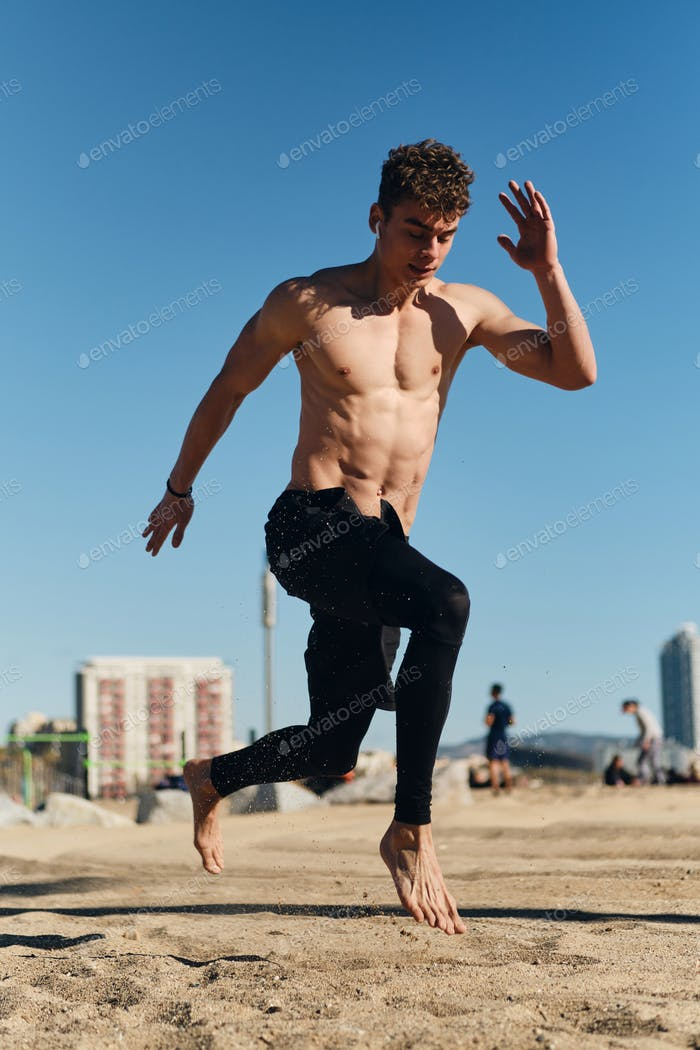 Handsome sporty guy jumping during functional training on beach. Young man on workout outdoor