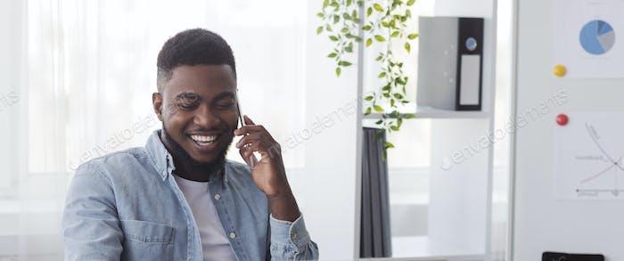 Feliz empleado negro hablando en el teléfono móvil en worplace en la oficina