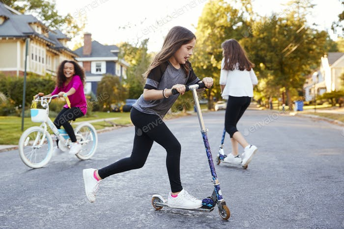 Girls playing in the street on scooters and a bike, close up
