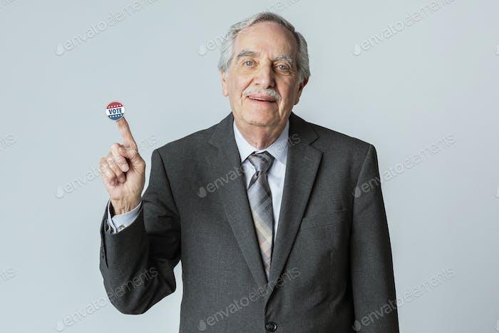 Feliz hombre de negocios con una pegatina de voto en el dedo índice