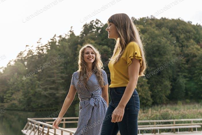 Strolling stylish women on pier in sunlight