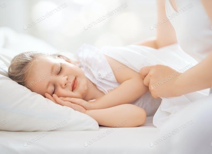 mother covering little sleeping girl