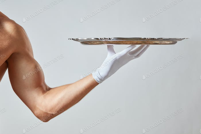 Muscular hand of waiter in a white glove holding a silver vintage empty tray on a white background