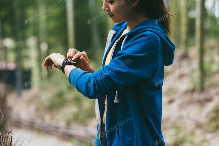 Young Asian woman using her smartwatch outdoors