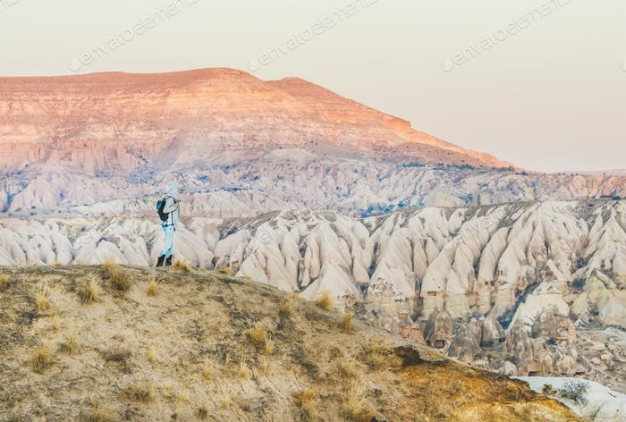 Young woman traveller hiking in mountains in Cappadocia, Turkey