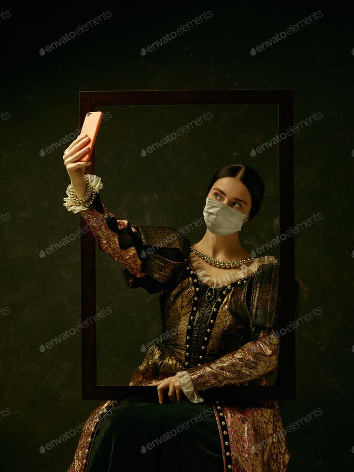 Medieval young woman as a duchess wearing protective mask against coronavirus spread