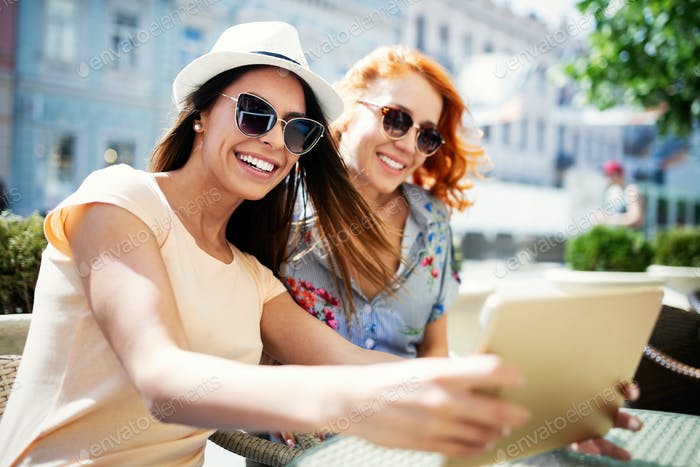 Happy young women using digital tablet in cafe outdoor