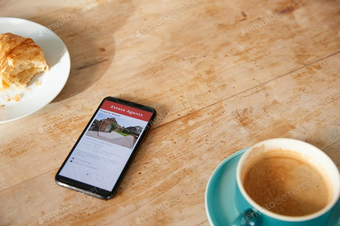 Close Up Of Mobile Phone With Realtors Property App Lying On Café Table