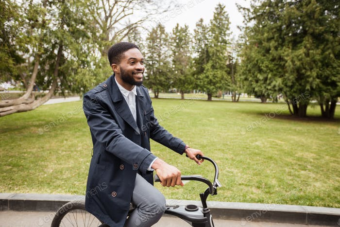 Excited afro businessman riding on bicycle to work, free space