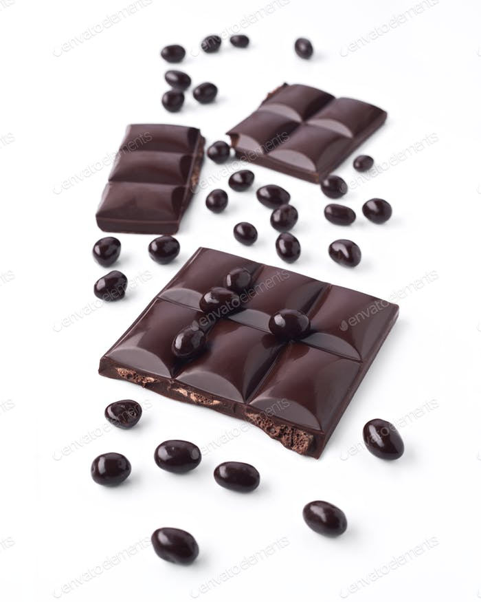 broken tablet of dark chocolate and chocolate balls, isolated on white background