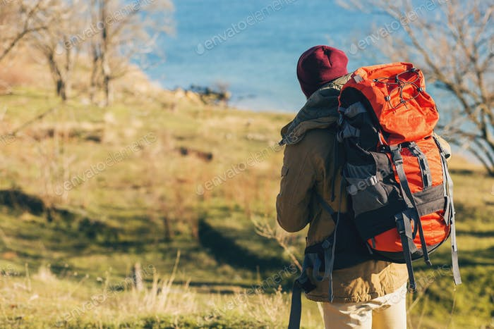 young hipster man traveling with backpack in cold season
