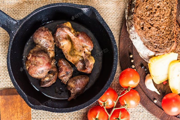 Top view roasted chicken giblets in pan and bread
