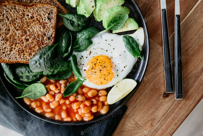Healthy breakfast or lunch at home or cafe with fried egg, avocado, toasts, beans and fresh spinach