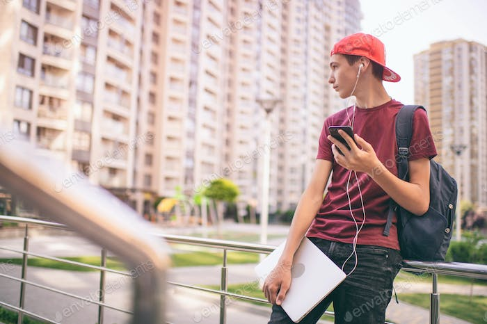Young man  stands with backpack and holds smartphone, in the city.