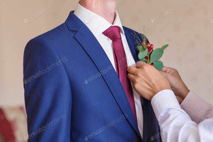 Best Man Adjusting Groom's Boutonniere close-up