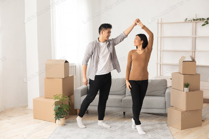 Happy asian man and woman dancing in new flat