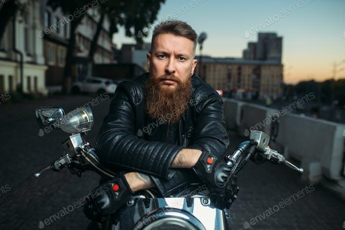 Brutal bearded biker poses on chopper, front view