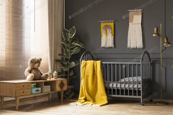 Real photo of a cot with a yellow blanket standing between a low