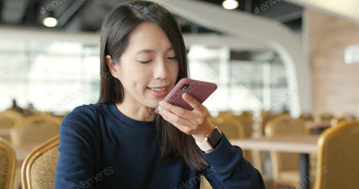 Frau senden Audio Nachricht auf Handy im Restaurant