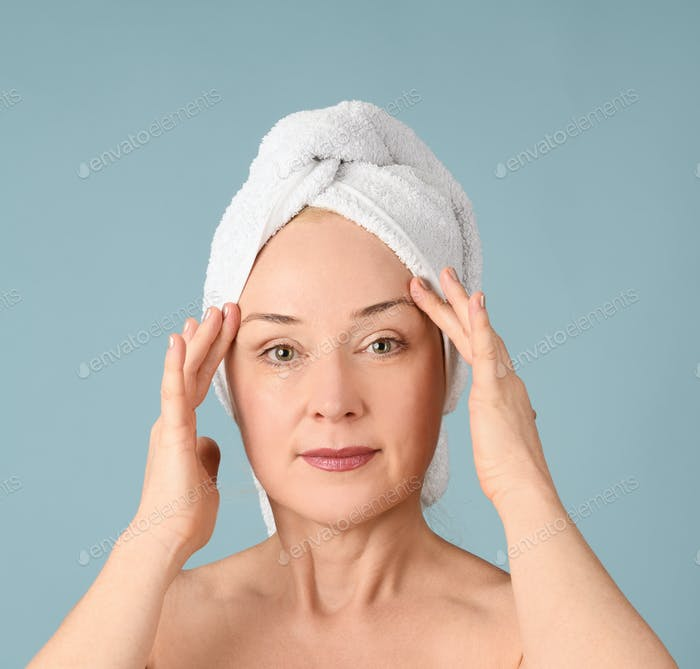Portrait of cheerful woman with towel on head