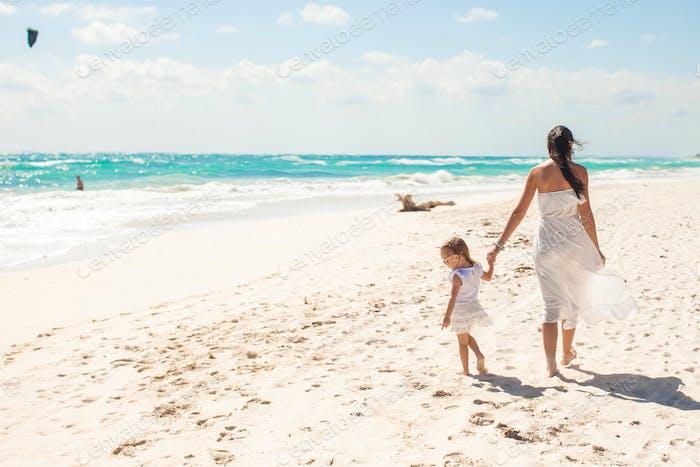 Rückansicht der jungen Mutter und ihre niedliche Tochter zu Fuß auf exotischen Strand