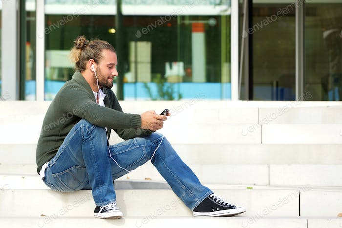 Young man sitting on steps listening to music with cell phone