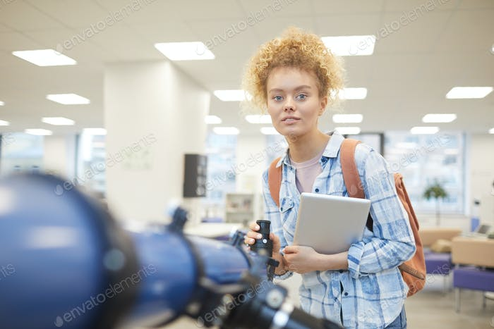 Student posiert mit Teleskop