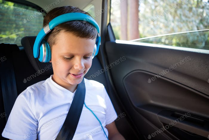 Teenage boy with headphones sitting in the back seat of car