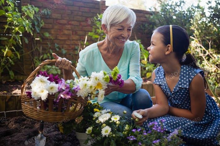 Lächelnde Großmutter mit Enkelin hält Blumenkorb