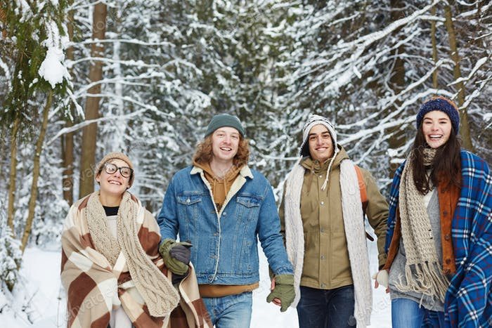 Happy Young Friends in Winter Forest
