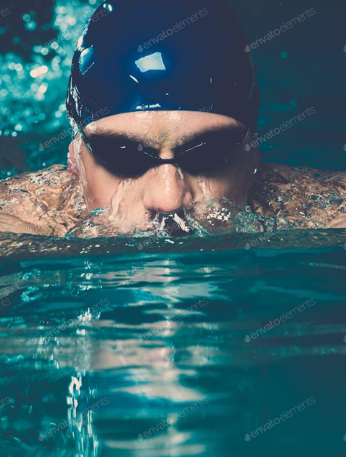 Muskulöser junger Mann in blauer Kappe im Schwimmbad