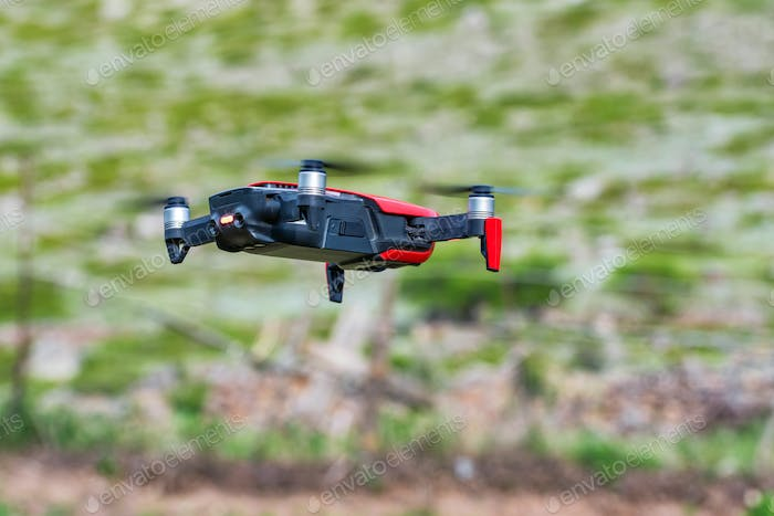 Modern dark and red drone in the air in mountains close