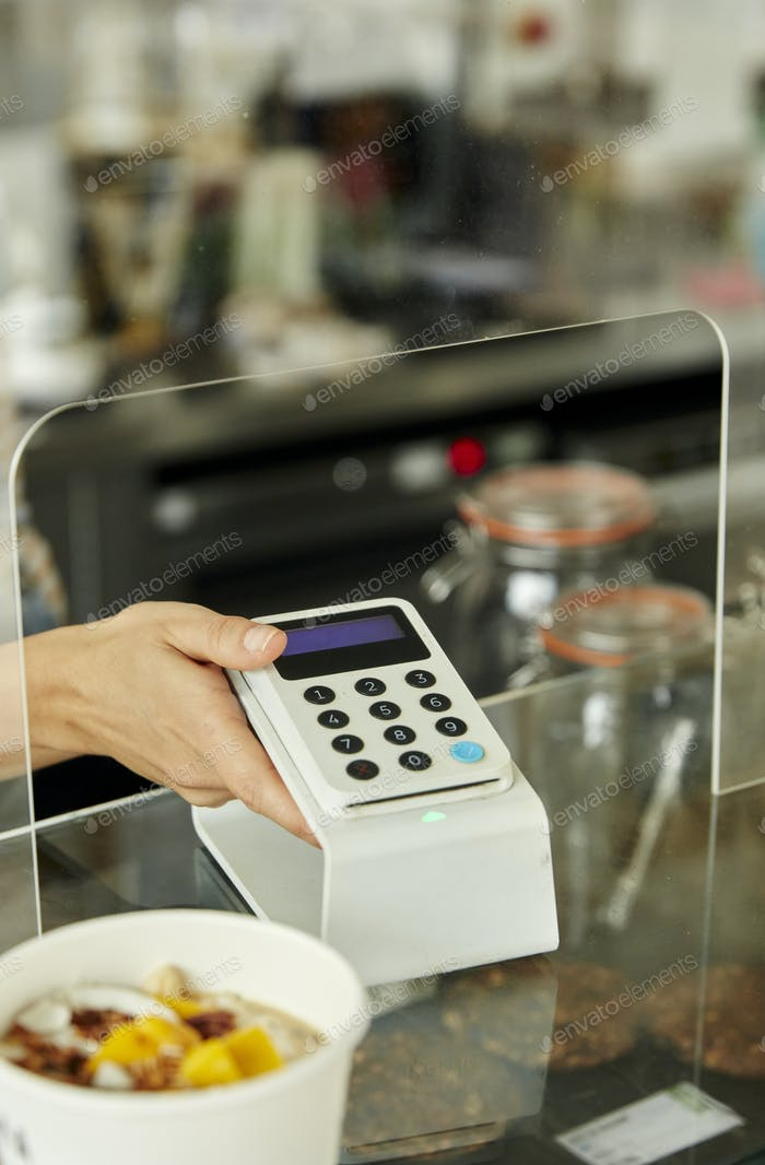 Womanwith a contactless payment terminal