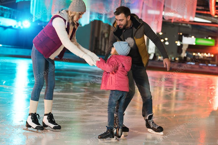 happy parents teaching adorable little daughter skating on rink