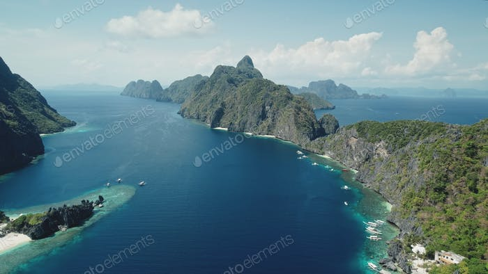 Mountainous island at tropical ocean gulf aerial shot. Birds-eye view of green forest hill in summer