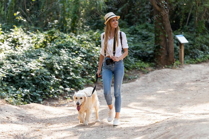 Attractive young amateur photograph woman walking with her lovely dog in the park.