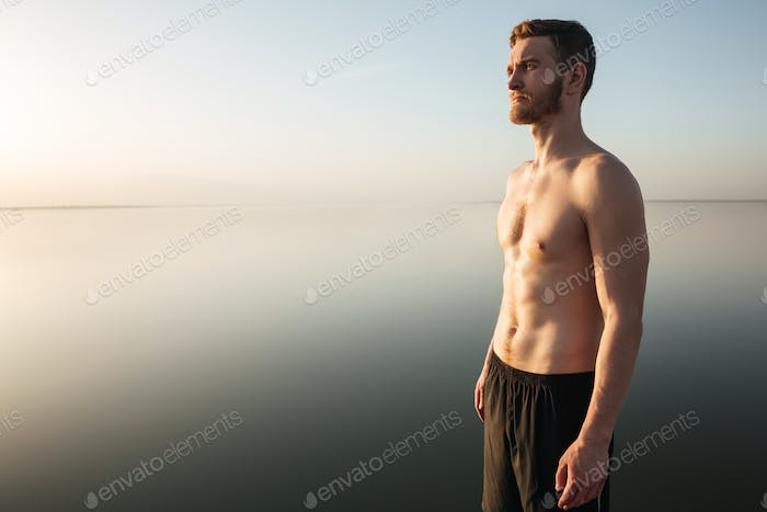 Portrait of a healthy shirtless sportsman standing outdoors with water