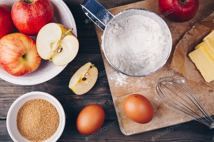 Ingredients for apple pie cooking with fresh red apples, butter, flour, eggs, brown sugar and spices