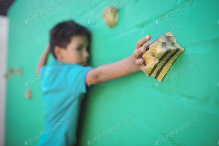 Boy climbing green wall