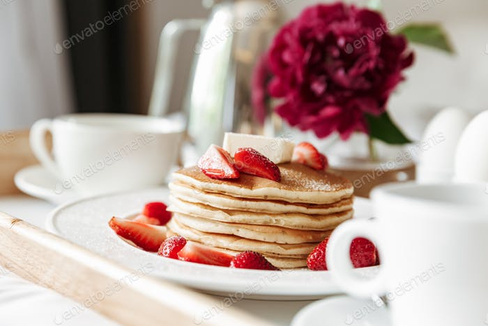 Closeup photo of breakfast in bed with white linen. Pancakes, bo