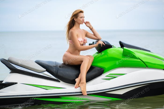 sexy woman in bikini on water scooter in sea summer style
